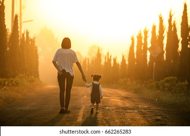 Mother and little asian toddler girl walking together on the way at the sunset with copy space, view from the back