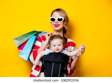 Mother and little baby in carrier have a shopping with bags. Models on yellow background