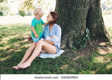 Mother with little baby daughter and older son on walking outdoor. Woman holding newborn baby with older child toddler on nature in the park. Family harmony life. Care and breastfeeding baby.