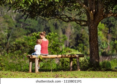 Mother, little baby son have fun outdoors, sit on bench under the tree on sunny lawn. Happy family lifestyle. Pretty young mom reading book to her child in park outside. Summer camp walks on vacation.