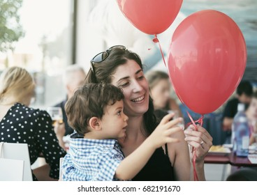 Mother and little boy playing with balloons in bar terrace