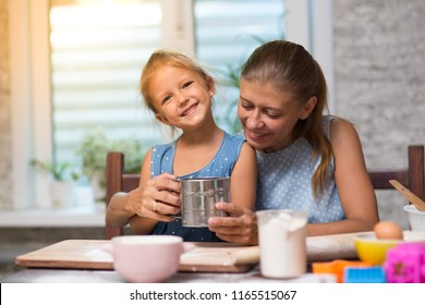 mother and little child daughter cook at home in the kitchen