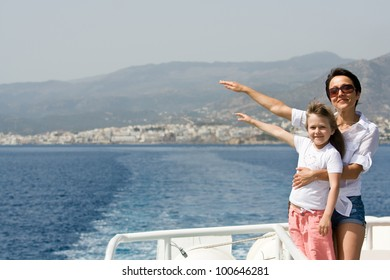 Mother, little child enjoy fresh summer wind and mountain seascape sailing by sea boat