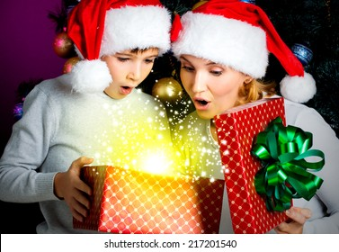 Mother with little child opens the box with gifts on the christmas holiday - indoors