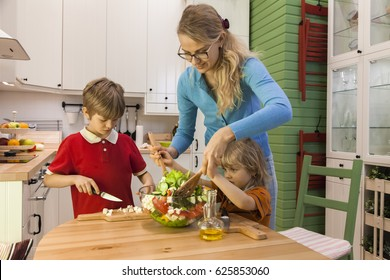 Mother and little child stirring vegetable salad. Kids helping Mom on the kitchen.