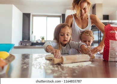 Mother and little children making cookies in kitchen. Siblings with rolling pin and flour helping mother in kitchen at home