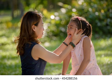 Mother and little cute daughter playing together in park, bokeh background