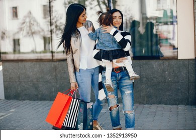 Mother with little daughter. Aunt with her niece walk in a summer city. Three girls have fun in a town.  Little girl with her two sisters