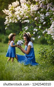 Mother and little daughter in blooming lilac garden with lilac bouquet. Mom loves her child. Spring story. Family look romantic similar blue dresses and straw hat. Happy family in beautiful spring day