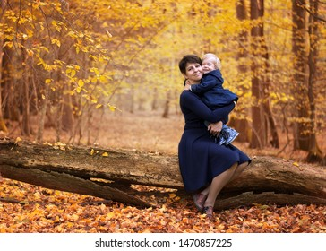 Mother and little daughter in blue dresses sitting on a fallen tree in a yellow autumn forest