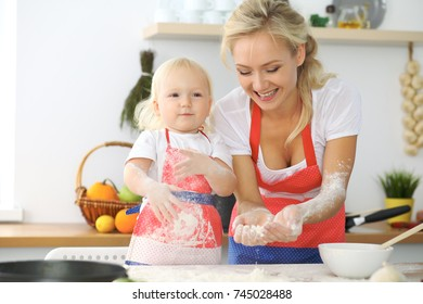 Mother and little daughter are cooking in the kitchen. Spending time all together or happy family concept