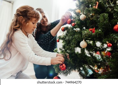 Mother and little daughter decorating Christmas tree at home. Little girl helping her mother in decorating Christmas tree.
