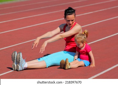 Mother and little daughter are engaged in running in the stadium. family doing fitness at the stadium