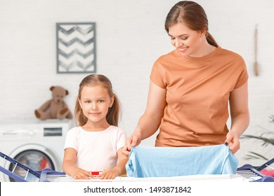 Mother and little daughter hanging laundry on clothes dryer after washing