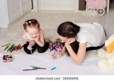 mother and little daughter having fun painting pictures