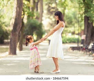 Mother and little daughter having fun in a park on a nice sunny day.