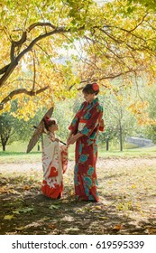 Mother and little daughter in Japanese kimono with umbrella in autumn Park