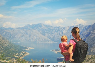 mother with little daughter looking at mountains on vacation