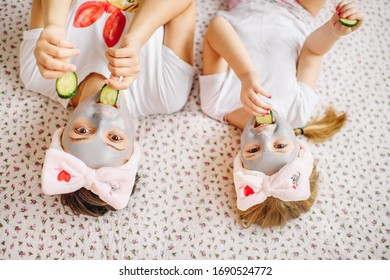 Mother and little daughter make a clay facial mask, family skin care at home
