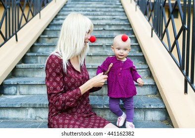 Mother and the little daughter with noses of clown sit in city park on steps