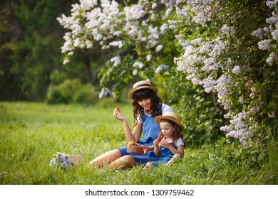 Mother and little daughter on picnic in blooming lilac garden. Mom loves her child. Spring story. Family look romantic similar blue dresses and straw hat. Happy family in beautiful spring day