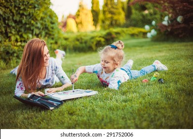 Mother and little daughter paint together outdoors