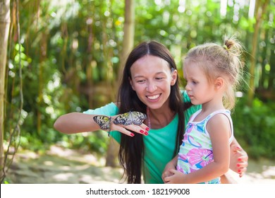 Mother with little daughter in the park butterflies