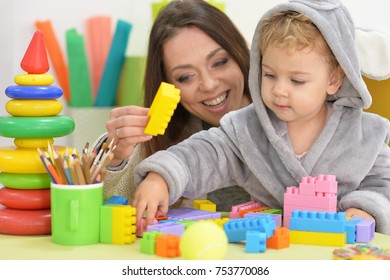 mother with little daughter playing with constructor