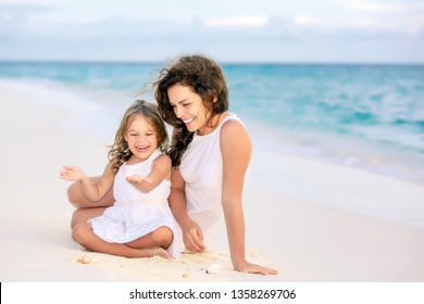 Mother with little daughter playing on ocean beach, Maldives