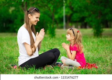 Mother and little daughter playing together in park. Outdoor Portrait of happy family. Happy Mother's Day Joy. Mom and Baby