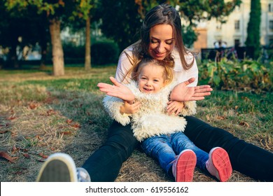 Mother and little daughter playing together in a park