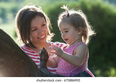 Mother and little daughter playing together in a park at summer time. Happy family lifetime concept.