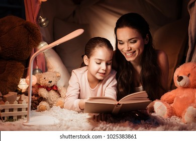 Mother and little daughter are reading book in pillow house late at night at home.