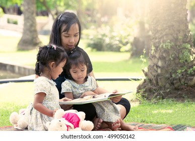 Mother and little daughter reading book together in the park