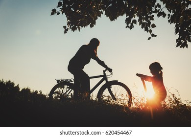 mother and little daughter riding bike and scooter at sunset