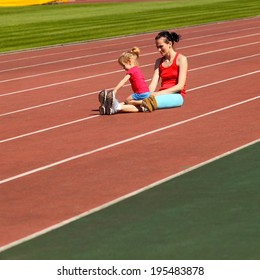 Mother & little daughter running around the stadium. Child runs away from mom at the stadium.