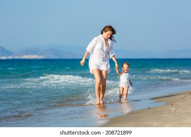 Mother and little daughter running on the beach