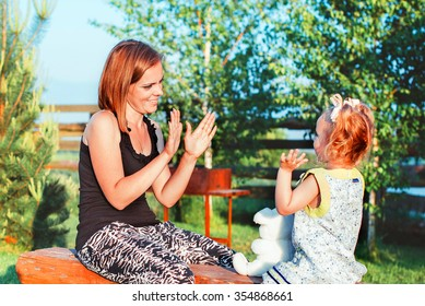 mother with little daughter sitting on a bench play, communication with children, leisure, children's entertainment