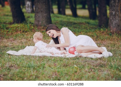 mother with little daughter sitting on a white plaid in the summer park