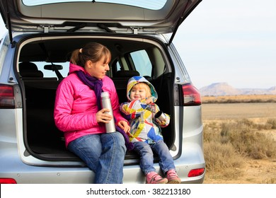 mother and little daughter travel by car in mountains