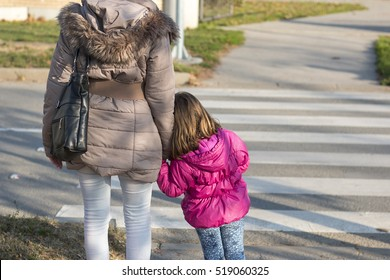 Mother with little daughter waiting to crosswalk street. Zebra crossing