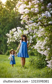 Mother and little daughter walk together in lilac garden. Mom loves her child. Spring story. Family look romantic similar blue dresses and straw hat. Happy family in beautiful spring day