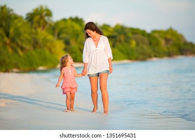 Mother and little daughter walking on sunny beach on Maldives at summer vacation