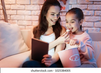 Mother and little daughter watching movies on tablet eating popcorn at night at home.