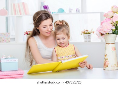 mother with little daughter in a yellow dress reading a book. mom teaches daughter to read