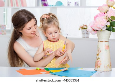 mother with little daughter in a yellow dress fun cut scissors colored paper