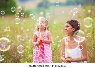 Mother and little girl daughter child blowing soap bubbles outdoor. Parent and kid having fun on meadow. Happy and carefree childhood. Good family relations.