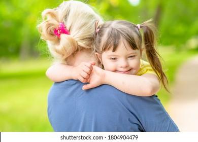 Mutter und kleines Mädchen mit Syndrom-Down haben Spaß im Sommerpark