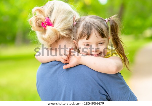 Mother and little girl with syndrom down have a fun in summer park