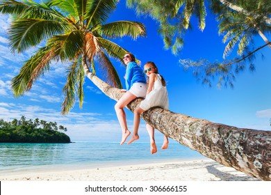 Mother and little girl at tropical beach sitting on palm tree during summer vacation
